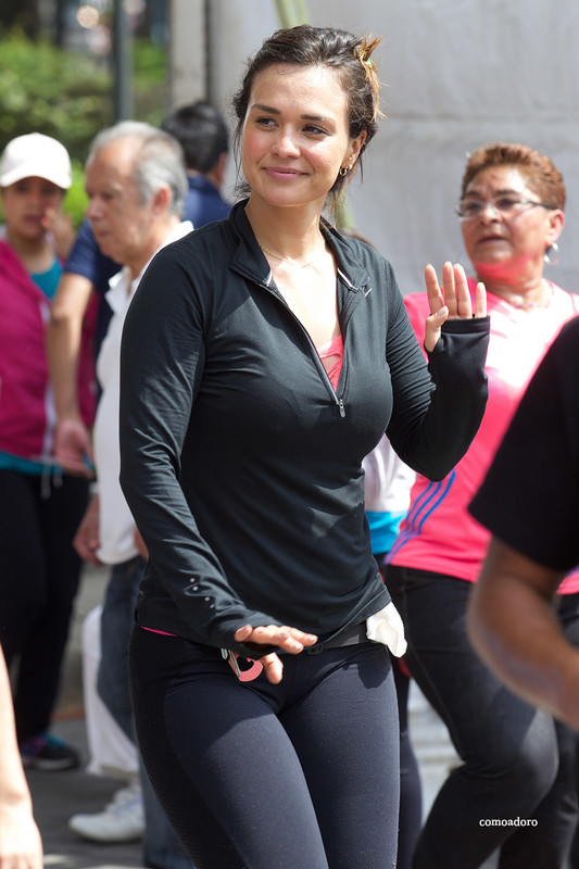 cheerful hispanic lady in sexy gym pants