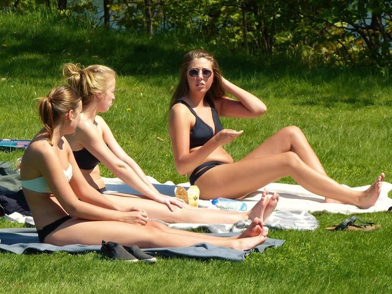 three coed girls sunbathing in city park