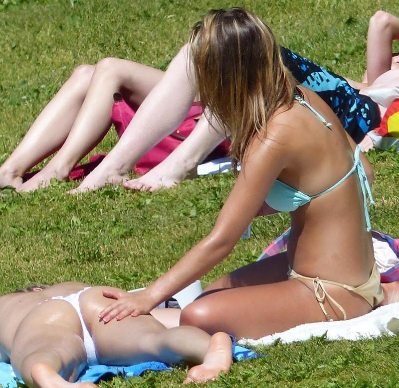 lesbian butt massage in a beach park
