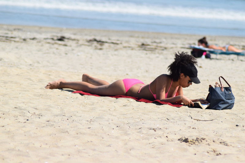 pretty african lady in pink bikini laying out in the sun