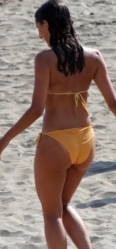 brunette female in wet orange bikini